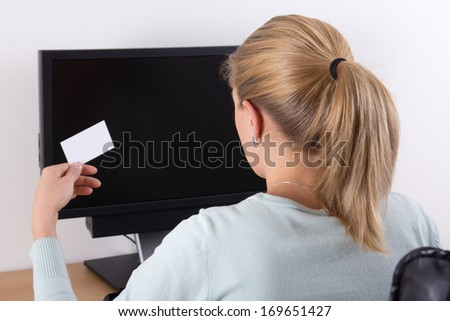 back view of young woman holding visiting card and using pc with copyspace on the screen - stock photo
