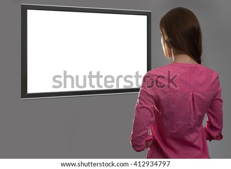 back view of young woman looking at blank tv screen with copy space - stock photo
