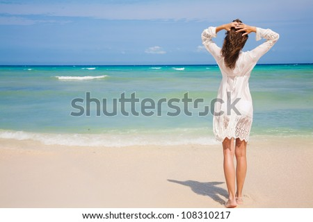 Back view of young woman looking at ocean - stock photo