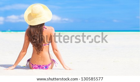 back view of young woman smiling in straw hat with closed eyes on the beach - stock photo