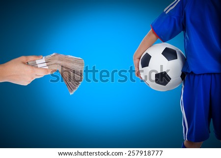 Back view of youth soccer player in blue uniform and little kid holding a ball and hand holding stacks of banknotes on blue background, Concept of achievements in business for soccer - stock photo