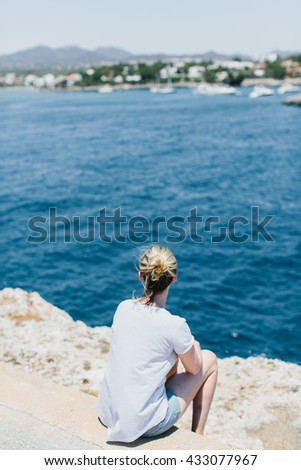 Back view on woman with tied hair, shorts and gray shirt looking over while seated on stones at waterfront with copy space - stock photo