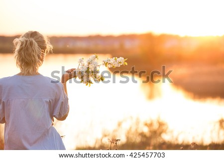 Back view on young woman by the lake on the sunset. Girl with apple trees flowers enjoying summer sunset in the park. Happy woman with bouquet, outdoors. Lifestyle and happiness concept - stock photo