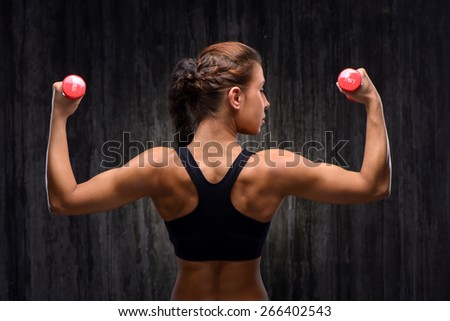 Back view photo of young mixed race sporty woman wearing black tracksuit for training. She holding red dumbbells and looking to the right. Fitness concept - stock photo