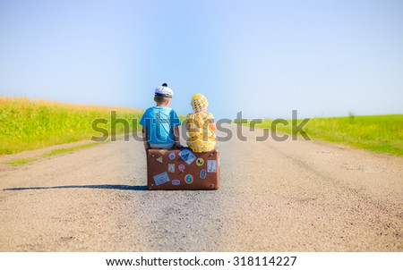 Back view picture of children sitting on the suitcase over countryside rural road on sunny blue sky outdoors background - stock photo
