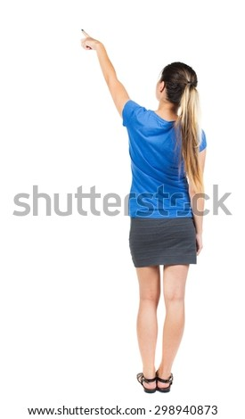 Back view pointing woman. beautiful girl. Rear view people collection.  backside view person. Isolated over white background. Girl in a gray skirt and blue T-shirt shows a finger of his right hand up. - stock photo