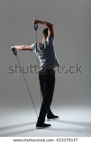 Back view portrait of a fitness man workout with expander over gray background - stock photo