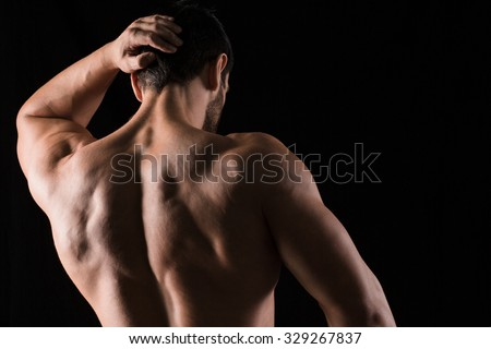 Back view portrait of a muscular man posing on black background - stock photo