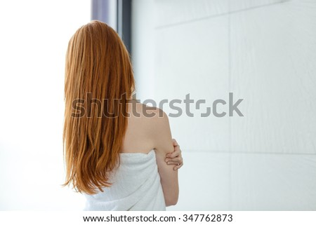 Back view portrait of a redhead woman in towel - stock photo