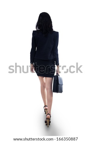 Back view portrait of businesswoman with briefcase walking - stock photo