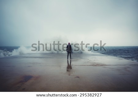 Back view portrait of young man standing against the sea on a large concrete pier with big wave beating with splash in a cloudy storm weather, feeling of freedom, male person enjoying rainy day alone - stock photo