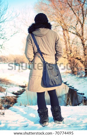 back view portrait of young woman on a moat watching sunset in winter park - stock photo