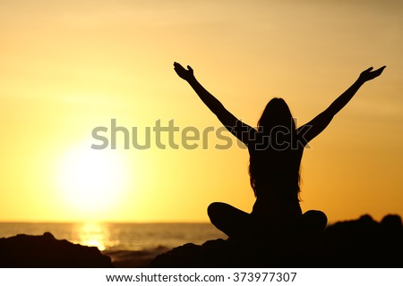 Back view portrait silhouette of a happy woman raising arms in a new day looking at warm sun at sunrise on the beach with the sea in a beautiful background - stock photo