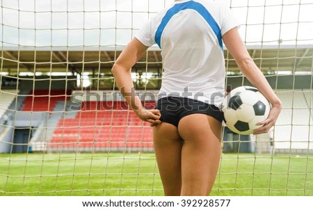 Back view. sexy Goalkeeper woman before a penalty kick. Empty stadium and blue sky with clouds on background. No face. Unrecognizable person. Space for inscription or objects. Big sexual ass - stock photo