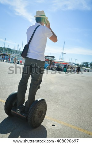 Back view silhouette of young man using segway and talking on mobile phone, video photo on the move. Person over sunny outdoors background  - stock photo