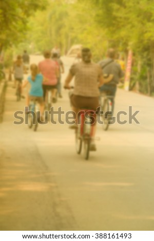 back view,the blurred of young parents with children ride bikes in park - stock photo