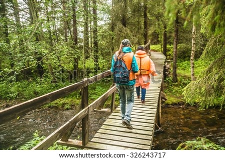 Back view. Tourists walking on a wooden bridge above mountain river with clear fresh water. Two woman going on floor from natural material. Summer wild forest Couple of girl wear jackets and rucksack - stock photo