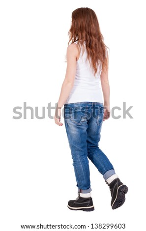 back view walking  woman . beautiful redhead girl in motion.  backside view of person.  Rear view people collection. Isolated over white background. teenager in black winter boots and jeans goes ahead - stock photo