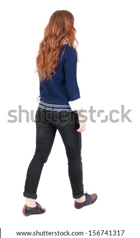back view walking woman. beautiful redhead girl in motion. backside view person.  Rear view people collection. Isolated over white background. girl in blue sweater and a white shirt is moving forward - stock photo