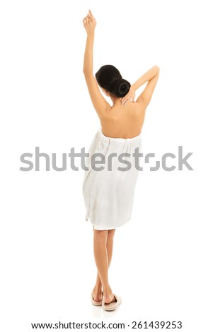Back view woman wrapped in towel stretching arms. - stock photo