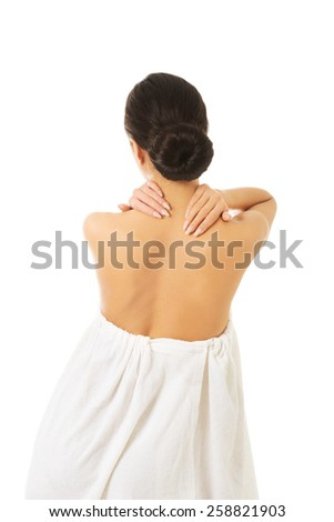 Back view woman wrapped in towel touching her back. - stock photo