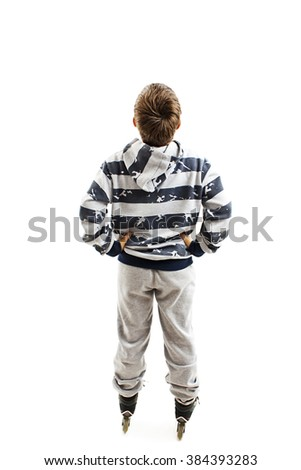 Back view young boy on rollers looking at wall. Rear view. Isolated on white background - stock photo