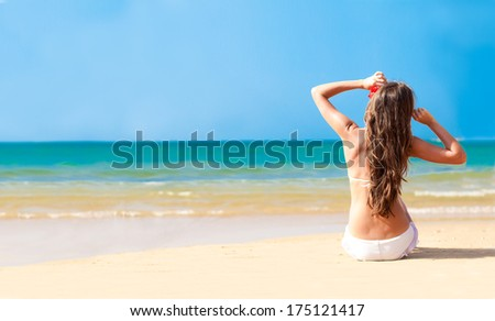 Back view young long haired woman in bikini and sunglasses with flower sitting on beach - stock photo
