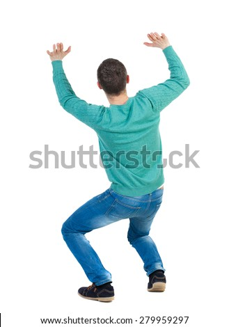 back viewman protects hands from what is falling from above. Man holding heavy load Rear view people collection.  backside view of person.  Man afraid of being crushed by a large weight. - stock photo