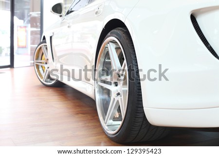 Back wheel of a bright white super car - stock photo