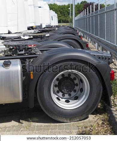 back wheels of a row white trucks - stock photo