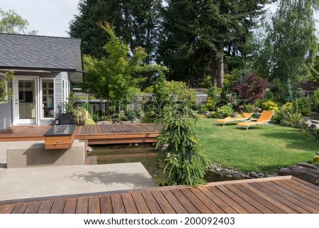 Back yard of a modern Pacific Northwest home featuring a deck spanning a creek-like water feature with a landscaped lawn and two inviting lawn chairs in the background.  - stock photo