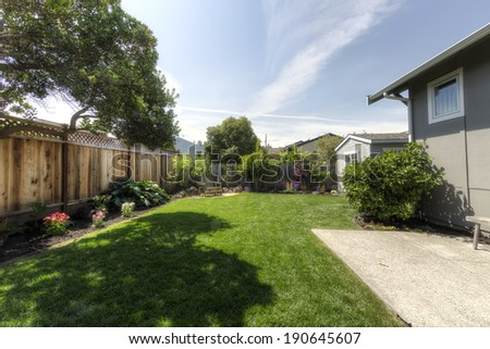 Back yard (or backyard) of common suburban home with green grass and blue sky - stock photo