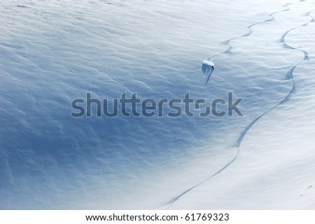 Backcountry skier riding down the huge snowfield splashing powder snow. - stock photo