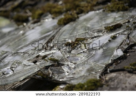 Background as broken pieces or crocks of white glass on the ground outdoors. - stock photo