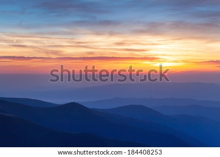 Background, beautiful, warm, bright colors of sunrise. In the mountains, stands a light mist over the countryside and the fresh air of freedom. Cloudy sky illuminated by the sun.   - stock photo
