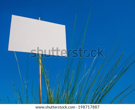 background blank advertising space in the green grass on a blue sky - stock photo