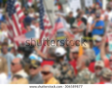 Background blur of crowd at political rally in the United States holding signs and carrying US flags. Great image for upcoming election cycle in 2016 presidential campaigns. Copy space - stock photo