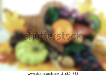Background blur of fall cornucopia containing fruits and vegetables and nuts with autumn leaves scattered around. Good background for fall, autumnal equinox, Halloween or Thanksgiving   - stock photo