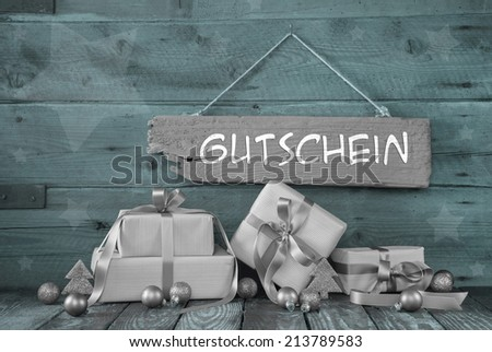 Background: Christmas voucher, coupon or bonus card with presents in grey, silver and mint green and text in german language. - stock photo
