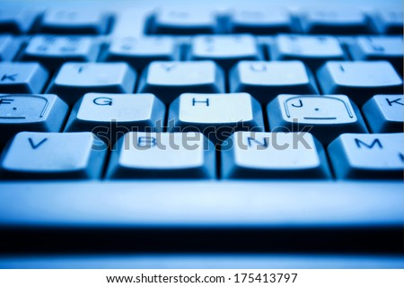 Background close up view of a computer keyboard in blue light with shallow dof - stock photo