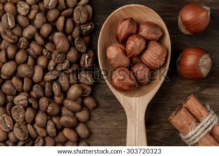 Background coffee. Roasted coffee, hazelnut, cinnamon on an old wooden background - stock photo