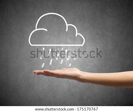 Background conceptual image with raining cloud in hand - stock photo