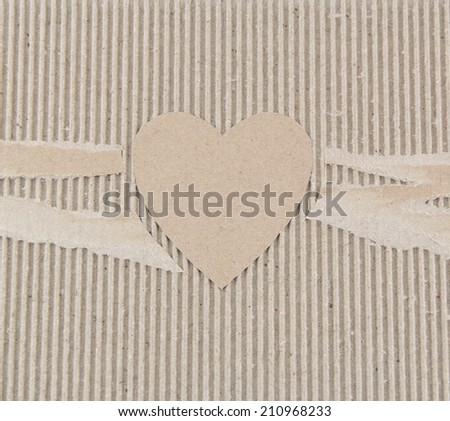 Background corrugated fiberboard heart is torn. Closeup background - stock photo