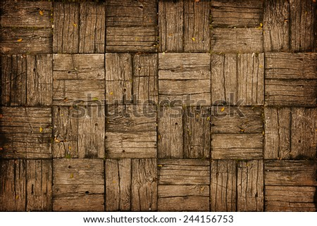 Background, depicting an old, weathered, parquet style wooden deck with alternating woodgrain pattern. - stock photo