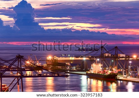 Background for cranes and industrial cargo ships in port at twilight. - stock photo