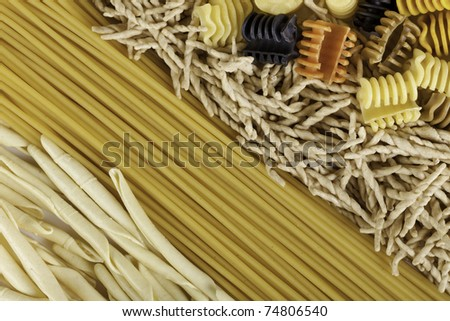 Background from several kinds of the Italian pasta. A shot vertical, focus in the middle of a shot. - stock photo