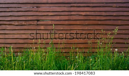 Background horizontal blank wooden fence overgrown with tall grass in the countryside close - stock photo