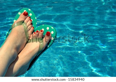 Background is filled with aqua water.  Woman has on polka dotted flip flops and has red painted toe nails.  Feet only. - stock photo