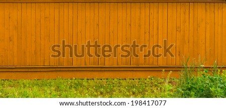 Background long blank wooden fence with grass in the countryside vertical made of planks - stock photo