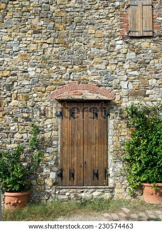 Background made by stone wall and wood door at Tuscany villa in Panzano in Chianti, Italy. - stock photo